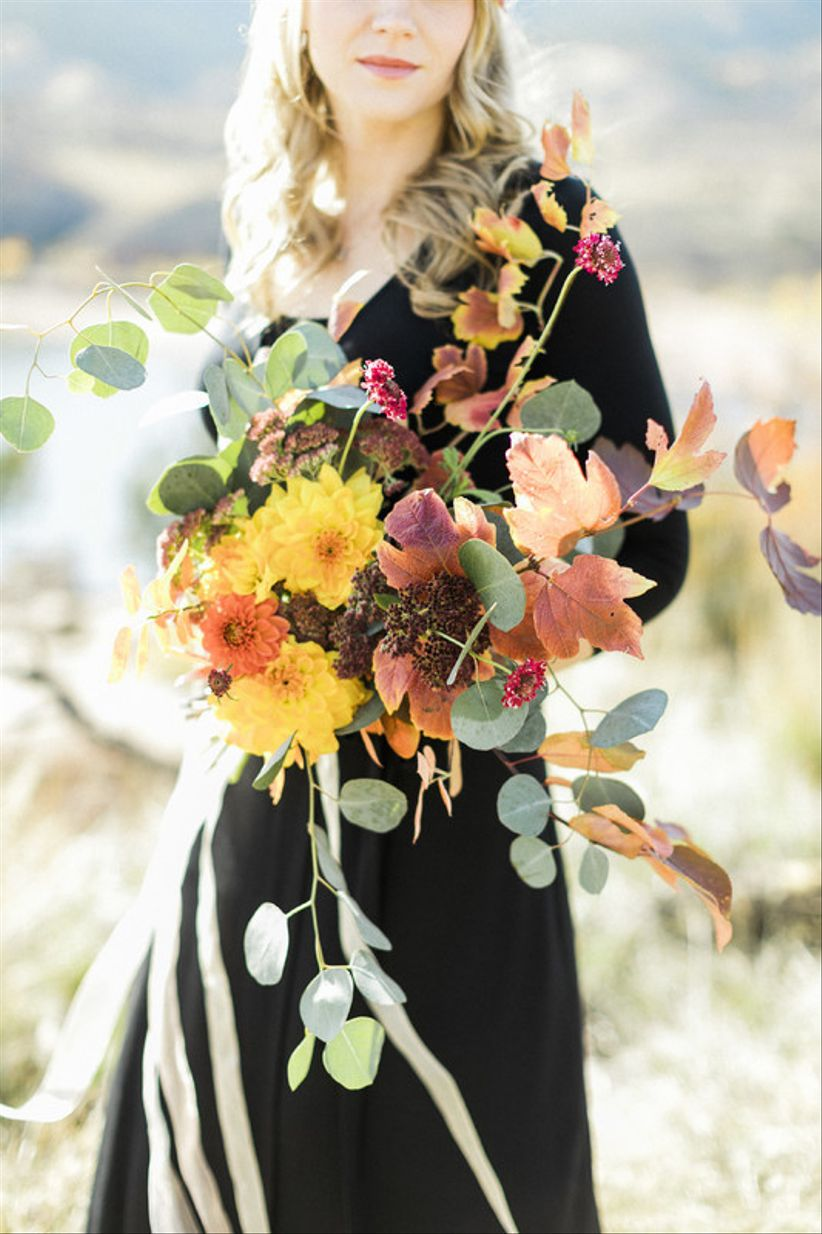 rustic fall bouquet with yellow and orange flowers and loose greenery