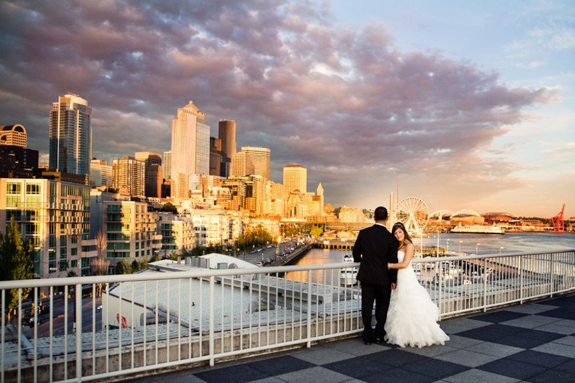 bride and groom pose with Seattle skyline and sunset in the background