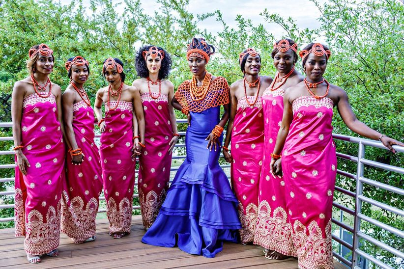 A Nigerian bride stands with her bridal party. All women wear bright coral headdresses and traditional Nigerian dresses.