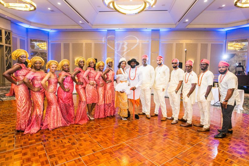 Different aso ebi styles are shown as Nigerian couples stands at a traditional wedding with their attendants.