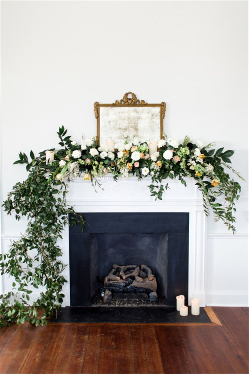 Romantic Indoor Wedding Venue With Fireplace Mantel Decorated With Flowers  And Greenery Garland With Candles