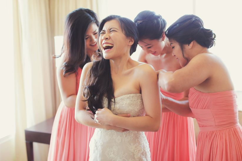 bride getting dressed with bridesmaids and laughing