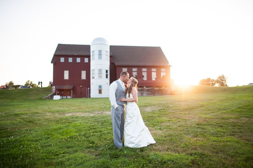 wedding couple kissing in front of barn