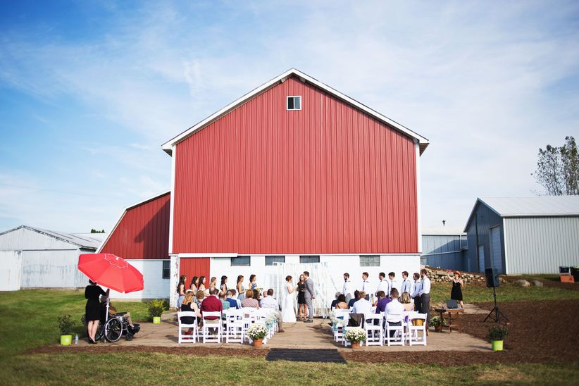 wedding ceremony outside a red barn