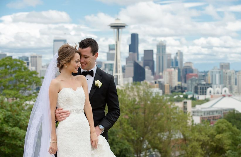 formal bride and groom pose for wedding pictures with Seattle skyline and Space Needle in the background