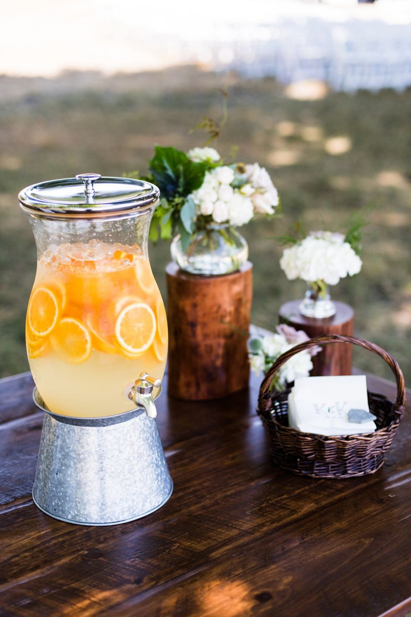 self-serve drink station at outdoor wedding reception with homemade iced tea