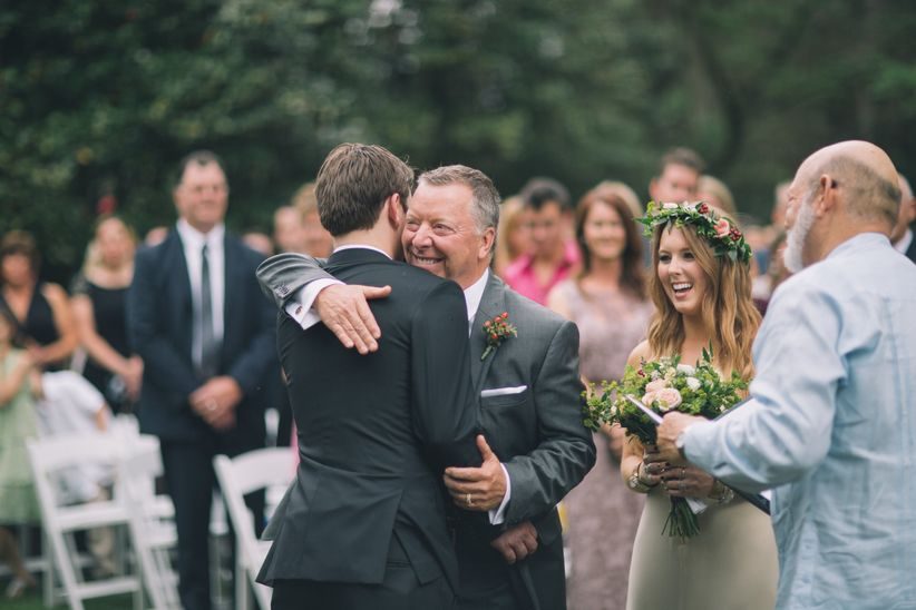father of the bride hugs groom during ceremony