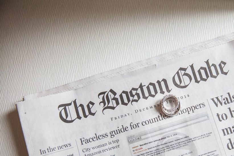 wedding rings atop boston globe newspaper
