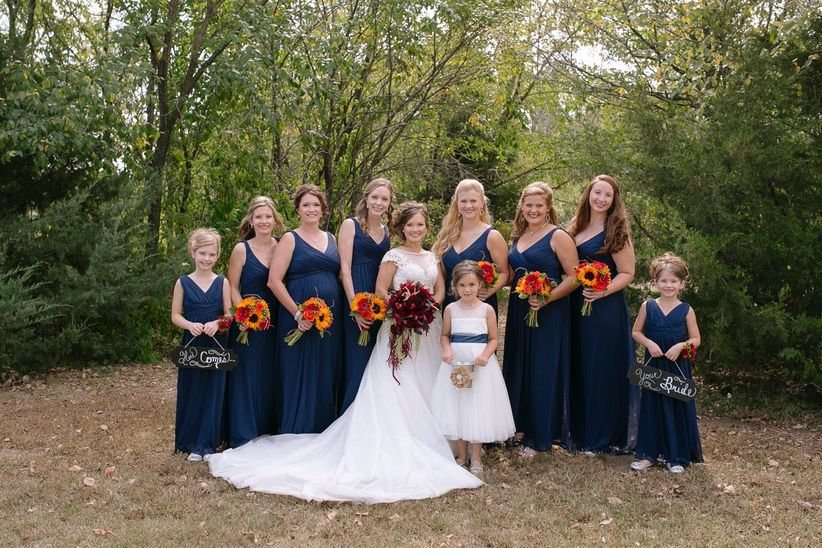 bridesmaids in navy gowns holding bouquets