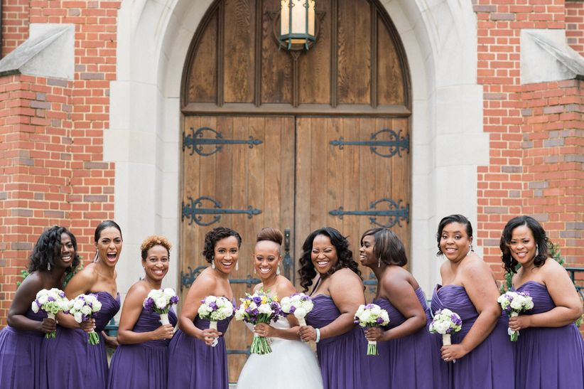 bridal party in front of church holding bouquets