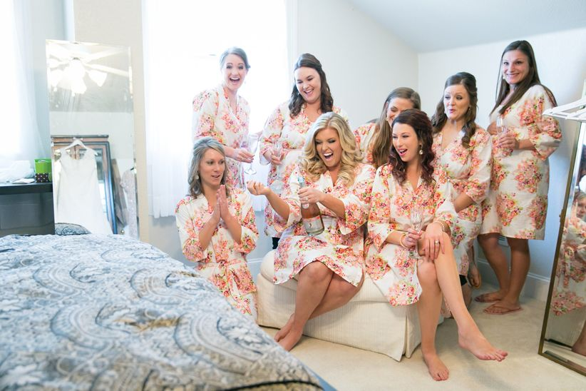bridesmaids in floral robes popping champagne