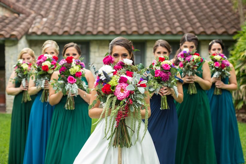 bridesmaids and bride hiding behind bouquets