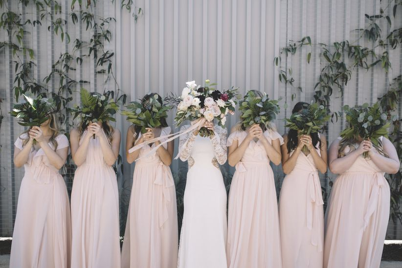 bridesmaids with bouquets in front of faces