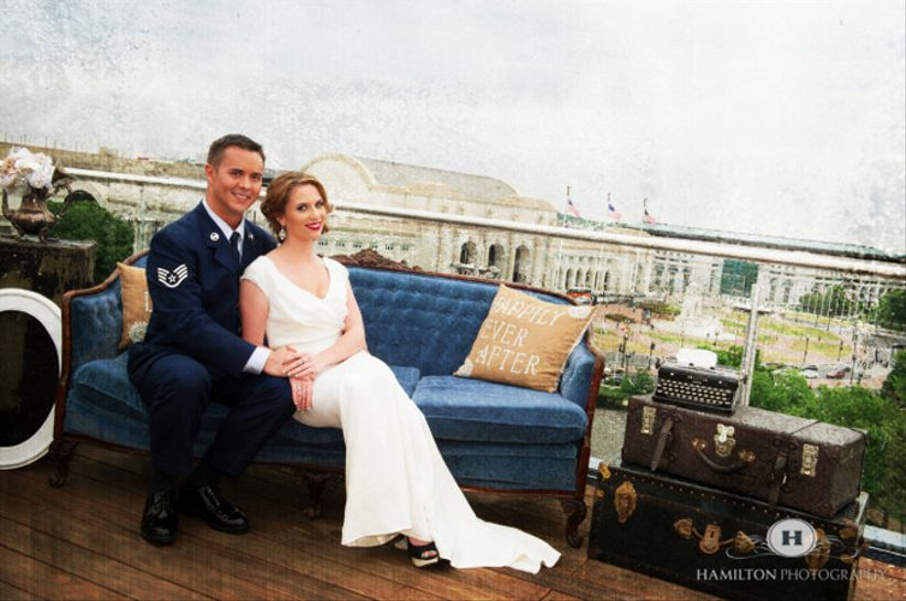 recently married couple sitting on a blue couch after their wedding at The Capitol View Rooftop. Union Station can be seen in the background.