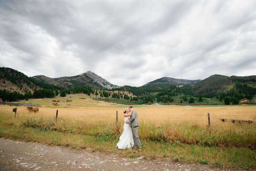 bride and groom pose on rustic cattle ranch at scenic montana wedding venue with mountains in the background