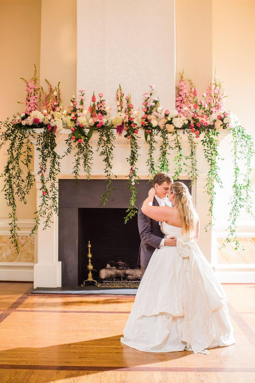 fireplace mantel at indoor wedding venue decorated with pink flowers and long greenery vines