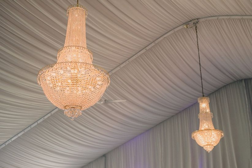 glamorous wedding reception tent with white drapes and crystal chandeliers