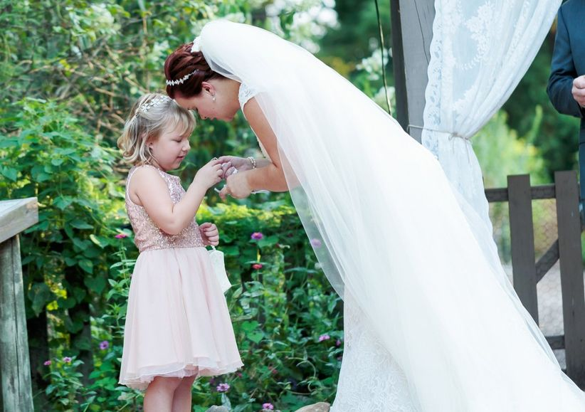 bride giving child ring during ceremony