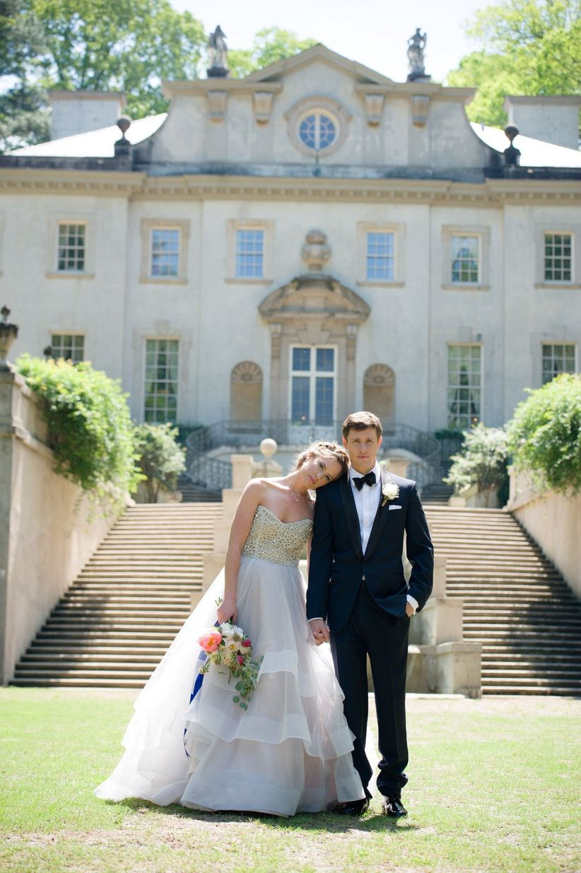 couple in formal attire in front of mansion