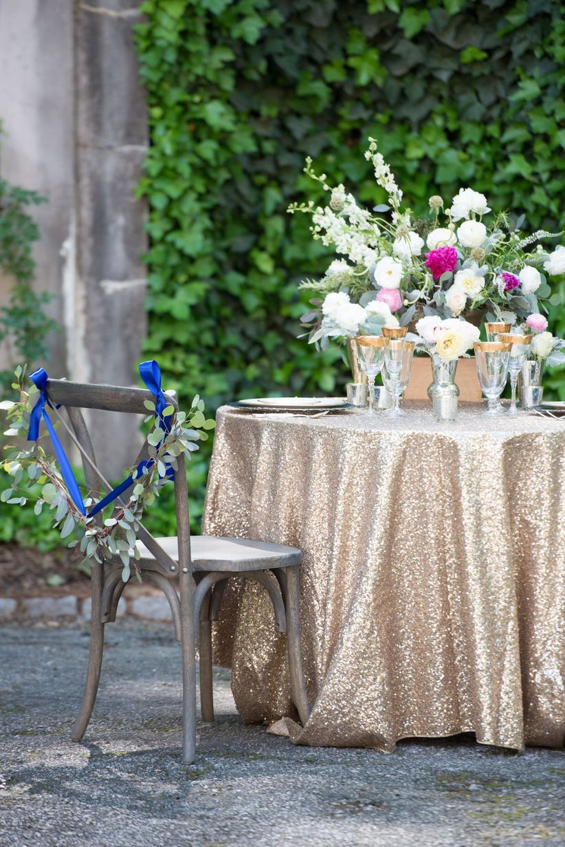 Close up cross back chair sweetheart table gold glitter tablecloth outdoors