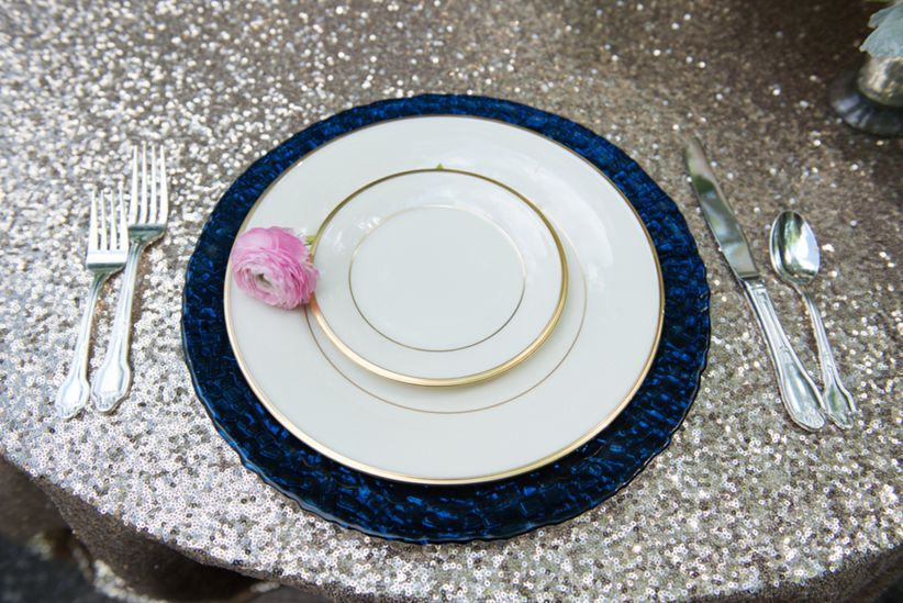 close up place setting white plates with gold rims and cobalt blue charger plate