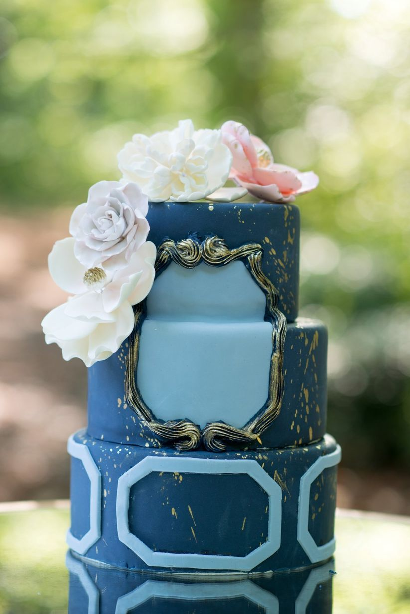 fondant wedding cake with dark and light blue icing muted gold details