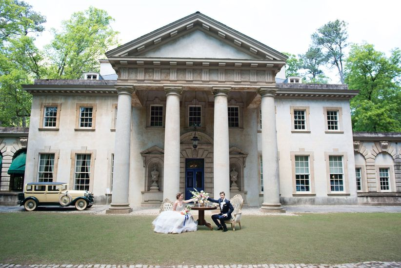 Wide shot couple at sweetheart table in front of mansion with vintage car out front