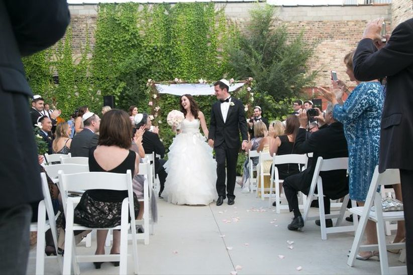 bride and groom recess down the aisle after their rooftop wedding at city winery in washington, dc