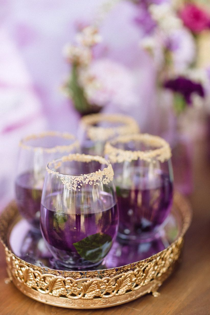 purple cocktails in gold-rimmed glasses