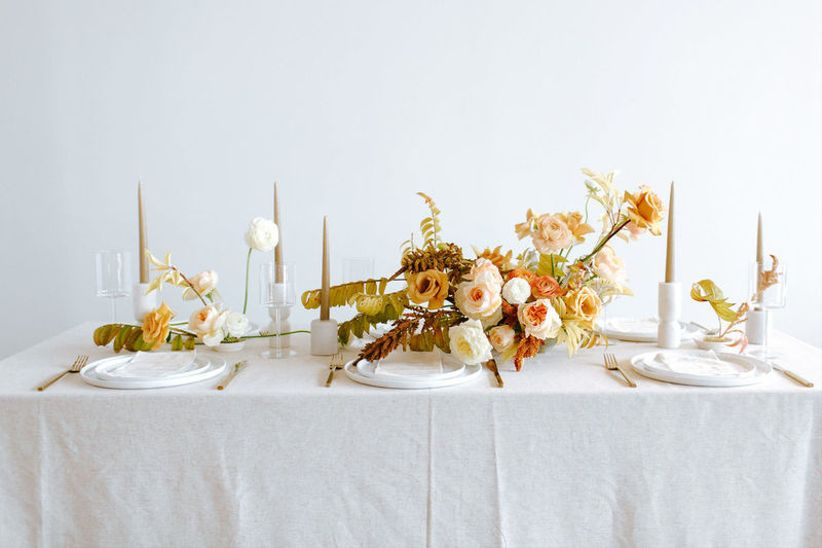 modern fall wedding centerpiece with pale yellow and orange flowers