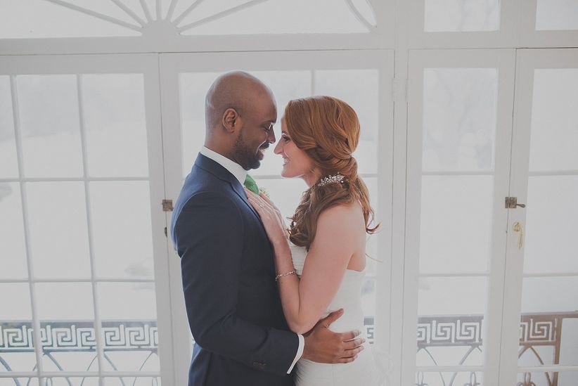 bride and groom standing in front of french doors