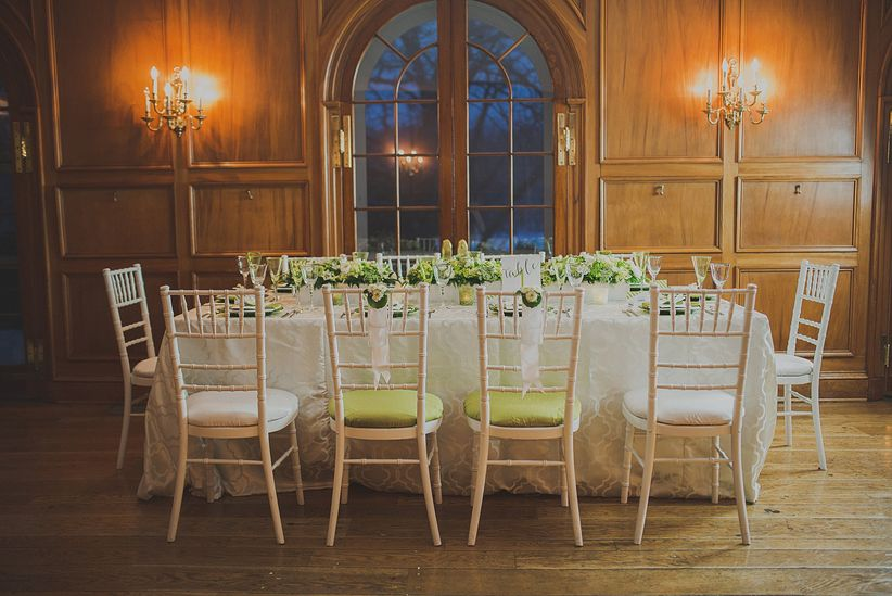 rectangle banquet table surrounded by chiavari chairs neutral colored patterned linens floral centerpiece mansion ballroom