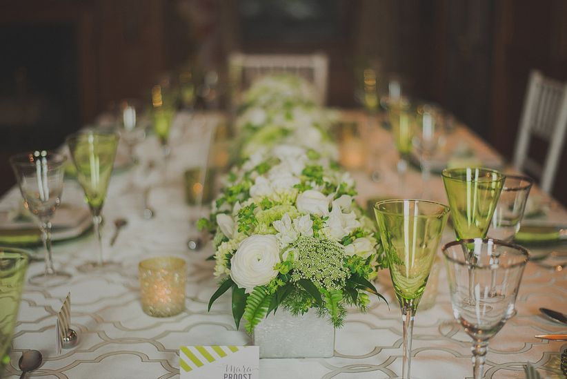 focus on floral centerpieces stretching along rectangle banquet table carnival glass place settings sparkly votive candles