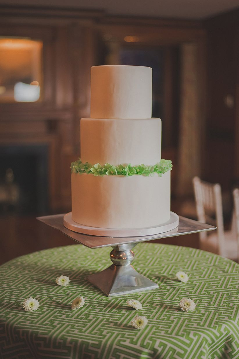 three-tiered white fondant wedding cake with green frosting around the top of the third layer on silver cake table green and white patterned table linens