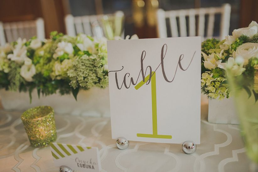 close up on modern table number in green white and gray sparkly votive candle long floral centerpiece