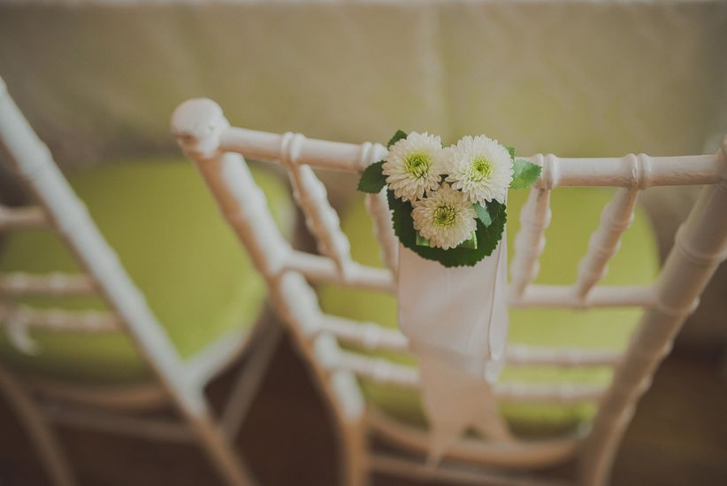 bride and groom's chiavari chairs decorated with small white mums and silk ribbon