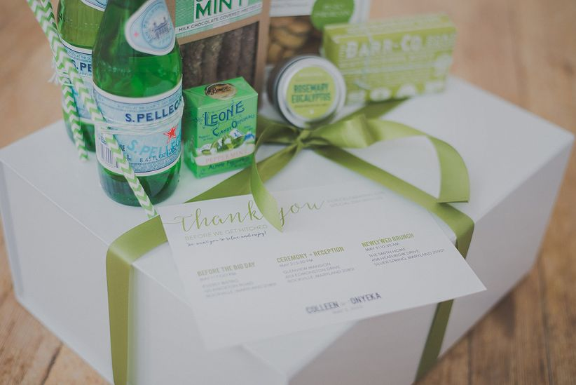 Close up large white boxes with green ribbon containing snacks and water for guests
