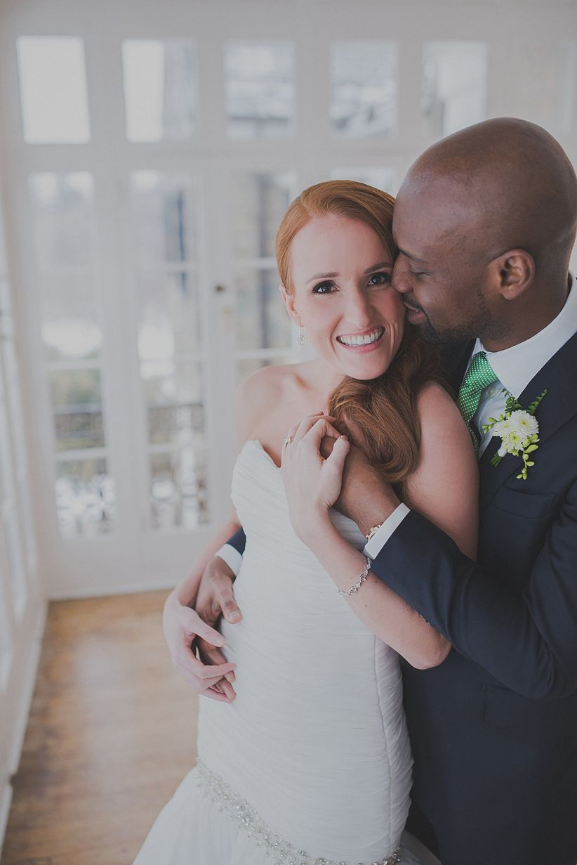 redheaded bride in strapless dress groom in navy suit with mint colored tie in front of french doors