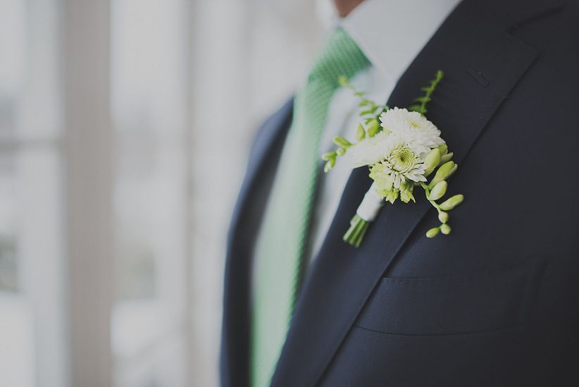 close up of groom's boutonniere featuring chrysanthemum navy suit mint striped necktie