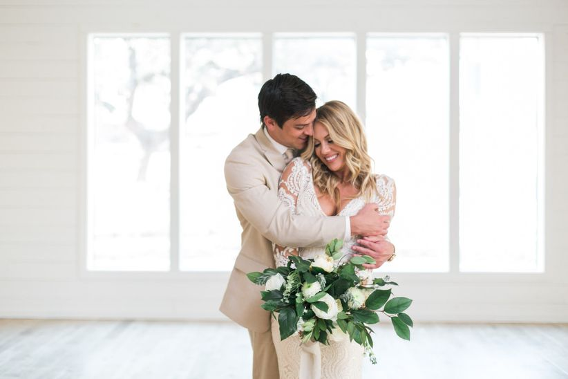 cute romantic candid photo of bride and groom hugging at modern rustic wedding venue