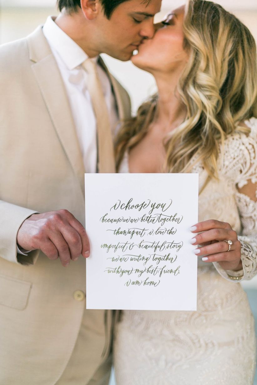 bride and groom kiss while holding wedding sign with romantic quote