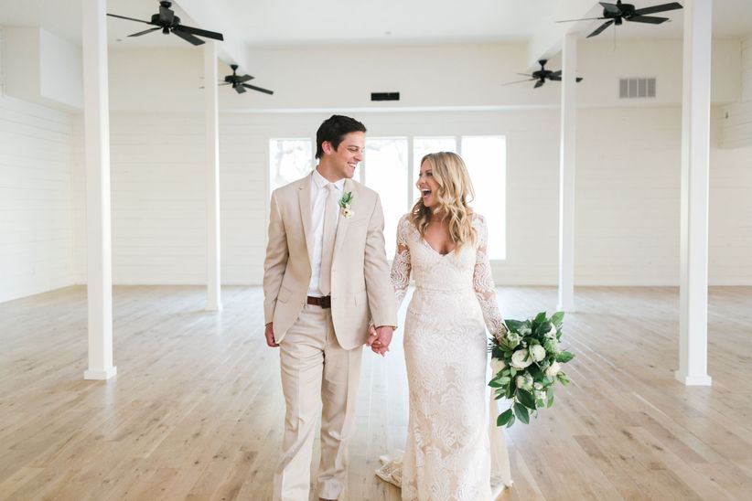 modern rustic couple holding hands at wedding reception