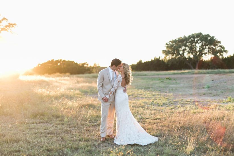 romantic rustic wedding photo idea with bride and groom kissing outside in a field at sunset