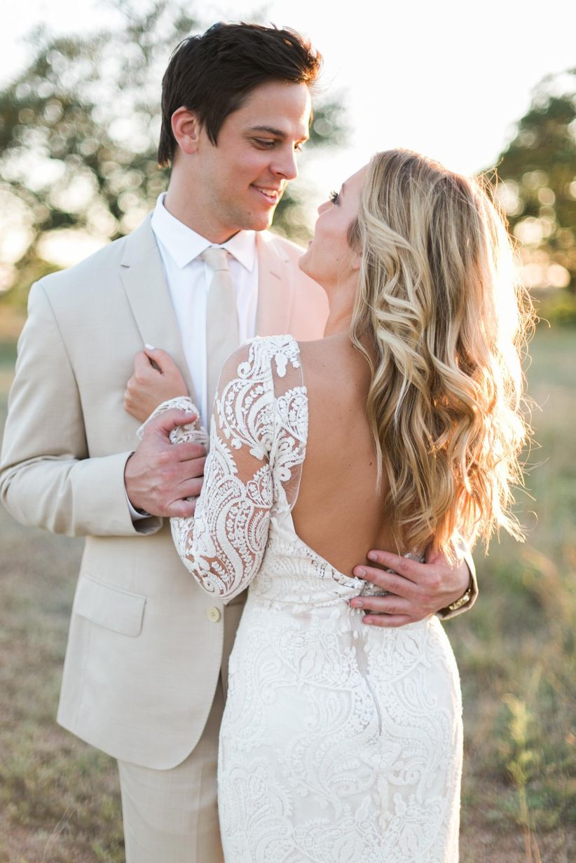 romantic photo idea for rustic wedding — bride and groom posing in a field at sunset