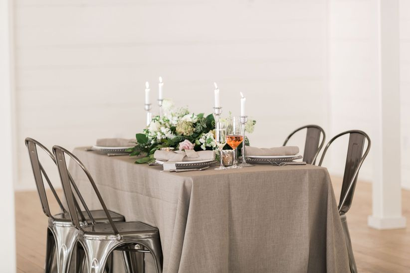 rustic farmhouse style wedding tablescape with neutral linens and blush and white centerpiece