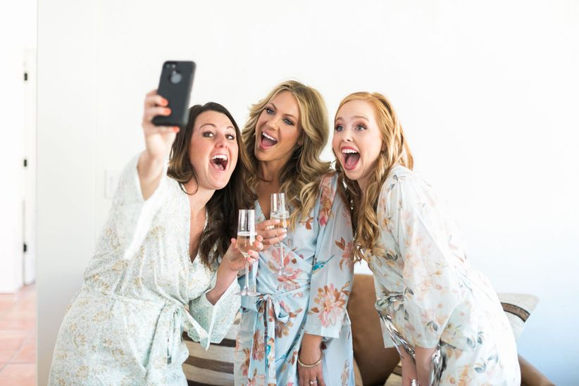 bridesmaids taking selfie with bride while getting ready and wearing matching floral robes