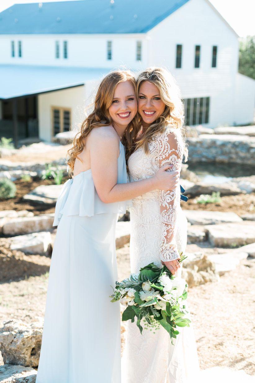 bridesmaid wearing light blue halter dress poses with bride wearing lace wedding dress with long sleeves
