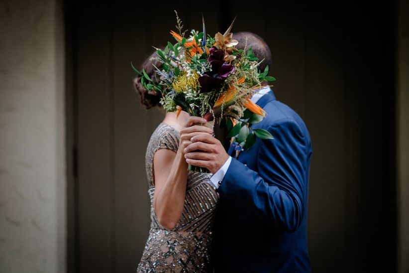 couple kissing behind bouquet