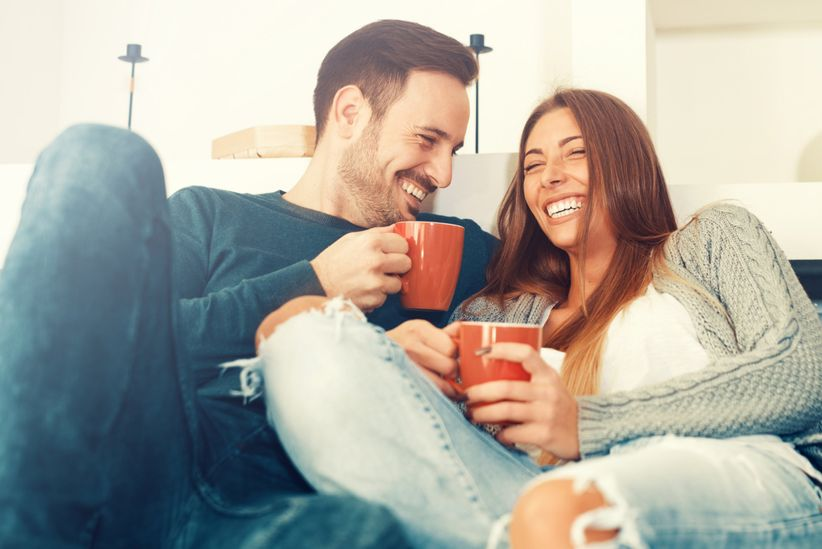 couple on couch holding red mugs