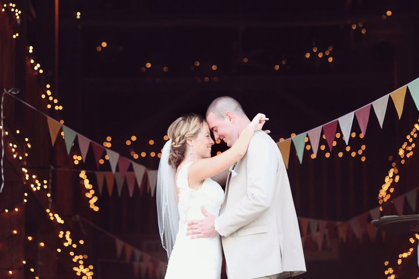 couple in front of barn and bunting